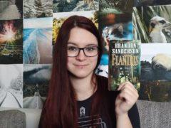 Kessy hält das Buch Elantris in die Hoehe und man sieht das Cover