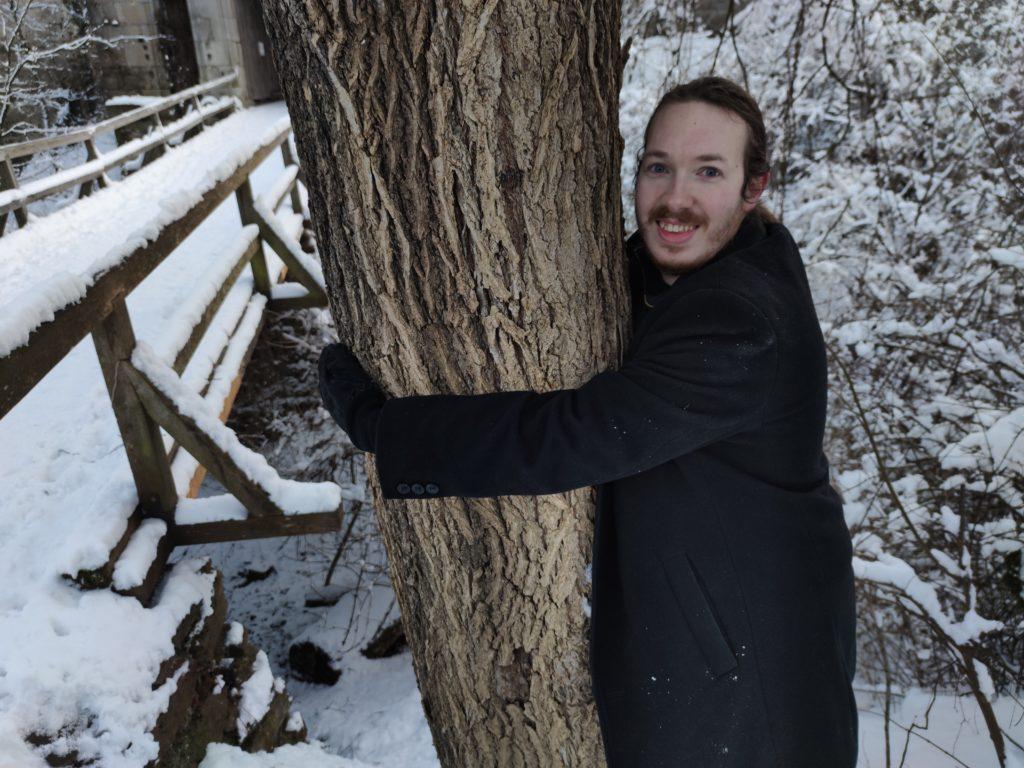 TreeHugChallenge Shanti umarmt einen Baum auf der Burgruine Schaunberg